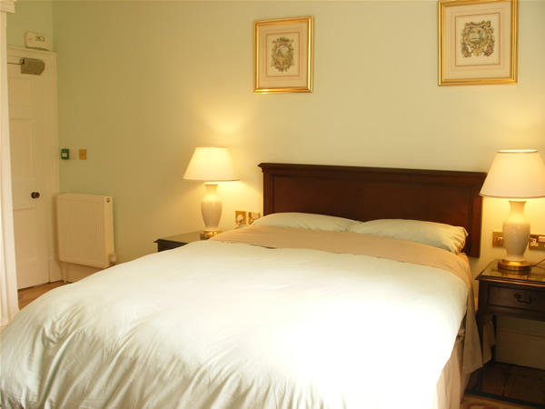 Photo of the standard king room which is lit by two cream coloured table lamps on Queen Anne styled bedside tables. The bed is made with duck egg blue and soft brown linen and the fixed rectangular mahoghany headboard with decorative beading on it edges is in the centre. Above are two gold colour framed printed pictures of pastel watercolour scenes surrounded by floral art.